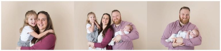 young parents holding baby girls in a photo studio