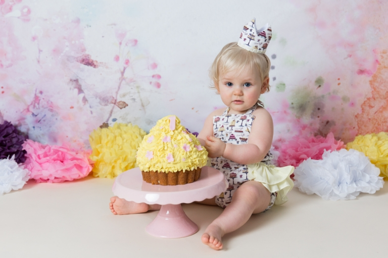 blonde toddler with first birthday cake smash in pinks and yellows