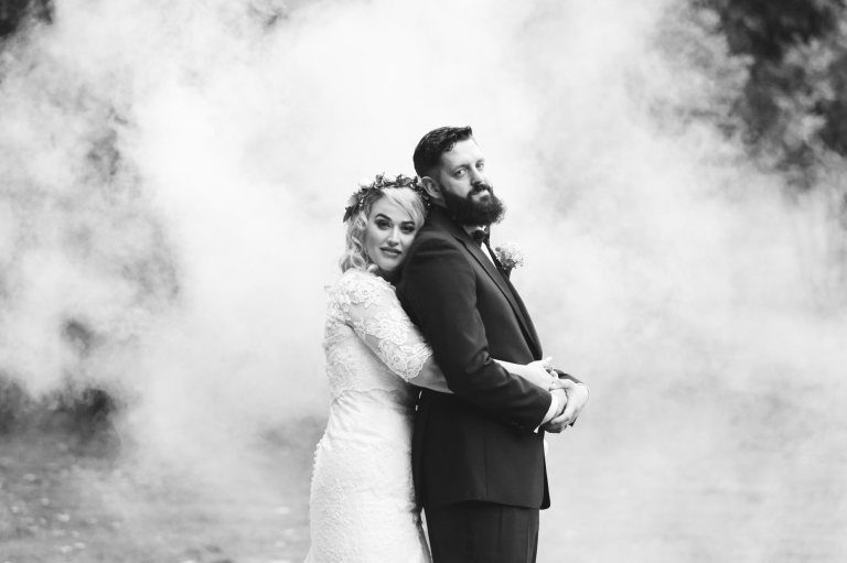 Alternative wedding - bride and groom cuddling in front of white smoke bomb